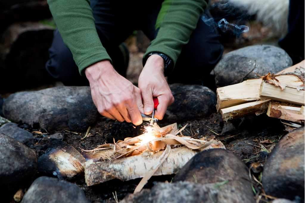 A mans hands are seen lighting a camp fire