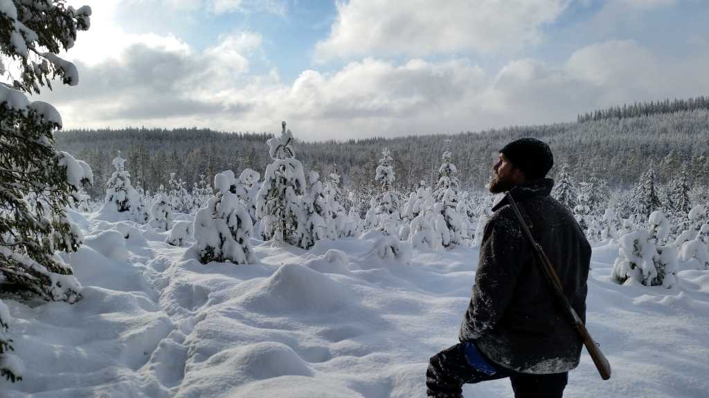 A man is looking out over a snowy landscape