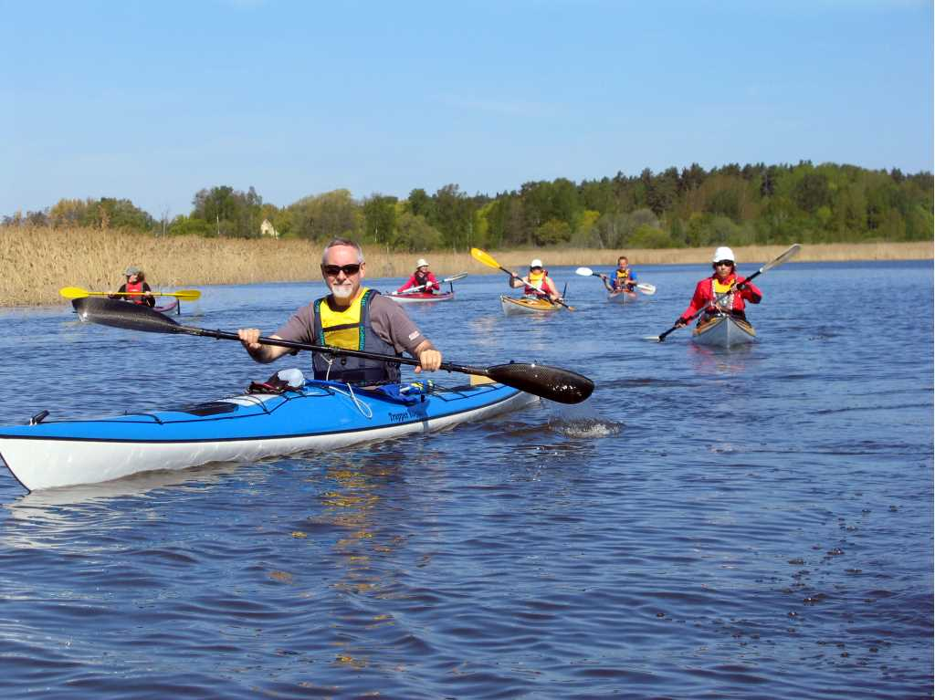 A group of peole are kayaking on a lake.