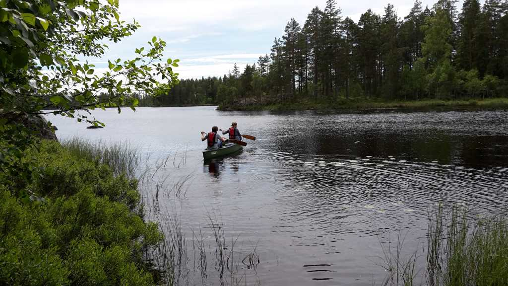 Two people in a canoe on a lake surrounded by forest